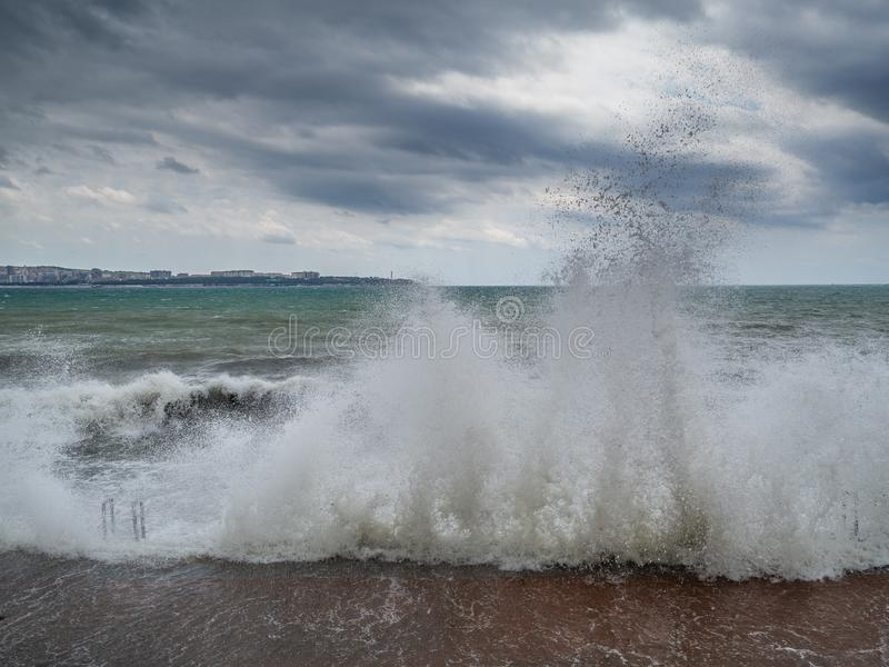 Storm on the resort coast. Storm waves are breaking on the pier. Dramatic cloudy sky and strong wind stock photo