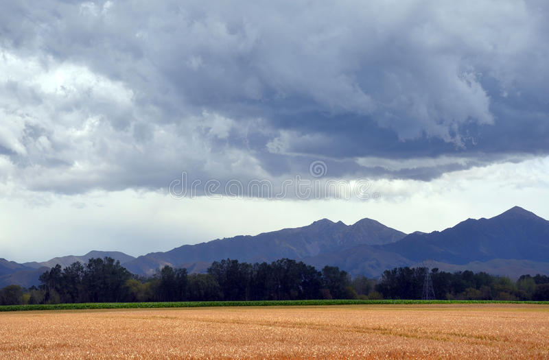 Storm rolling in over farmland. Storm rolling in over field in farmland. Dramatic sky with mountains in the background. New Zealand stock photography