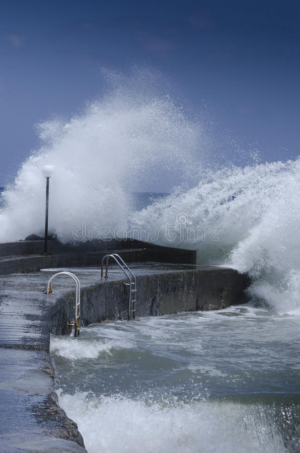Storm at sea. Big waves breaking on the pier with great spray royalty free stock image