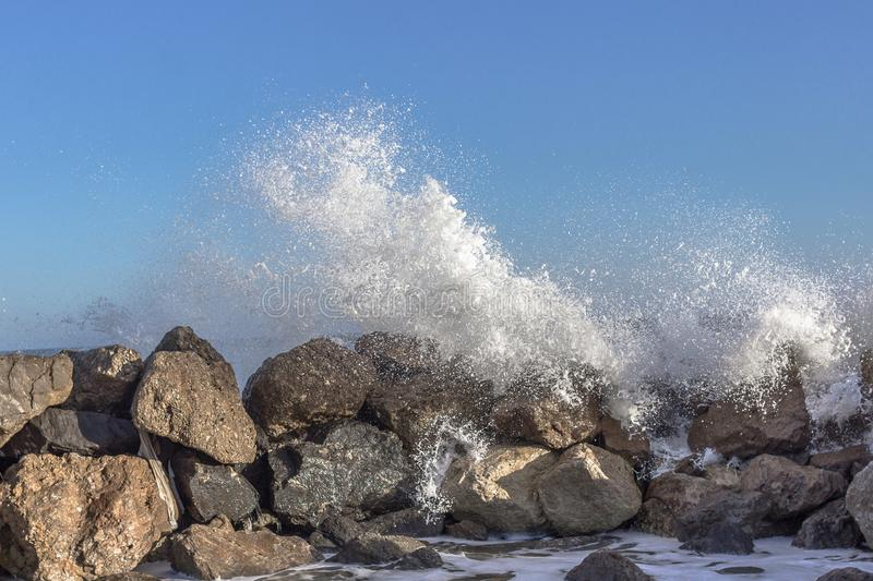 Big waves crashing on stones during a storm at sea royalty free stock photo