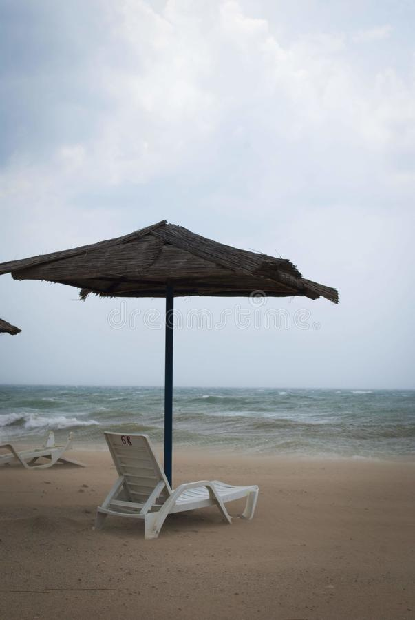 Storm on the sea with thunderclouds. Beach umbrella and inverted sun beds under umbrella on the beach. Storm on the sea with thunderclouds. Beach umbrella and royalty free stock photo