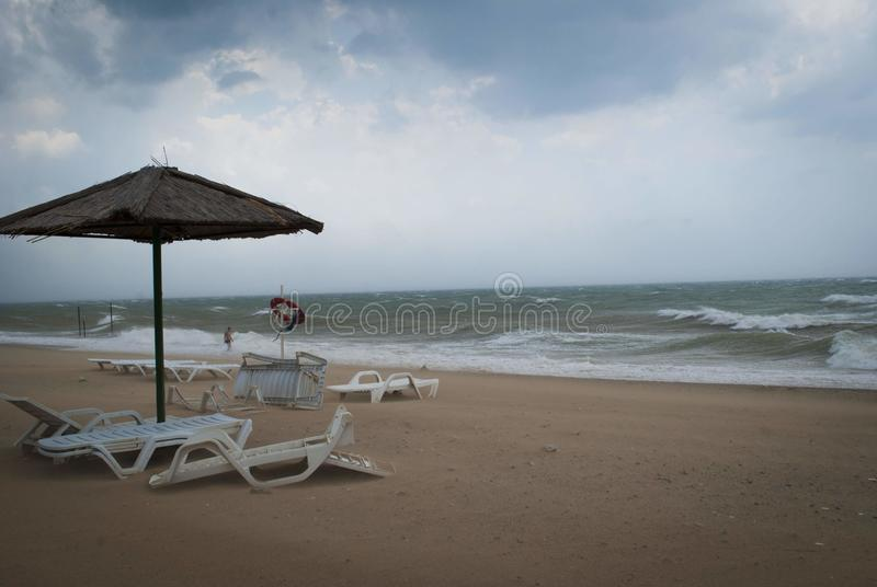 Storm on the sea with thunderclouds. Beach umbrella and inverted sun beds under umbrella on the beach. Storm on the sea with thunderclouds. Beach umbrella and stock photos