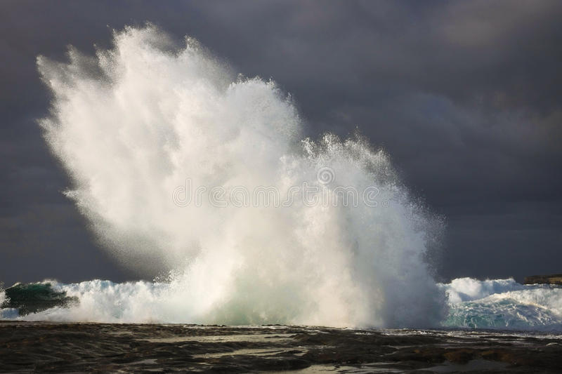 Storm seas and wave explosion. Wave from storm seas crashing onto rocks, causing explosion of water royalty free stock photography