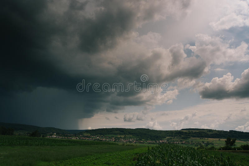 Storm sky. A storm sky with heavy clouds with some old houses and corn field in foreground stock photo