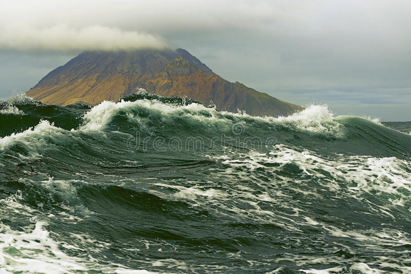 Storm surge on the background of the Kuril Islands stock image