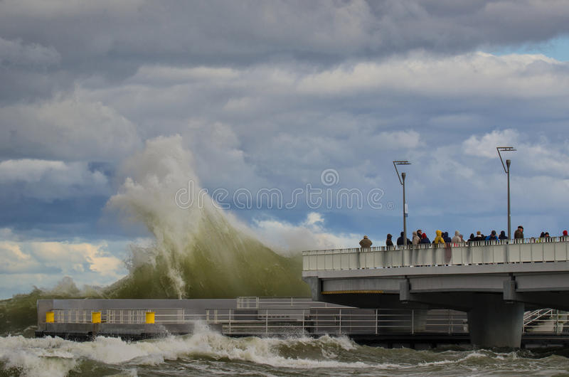 STORM SURGE AND PIER. KOLOBRZEG, WEST POMERANIA / POLAND: Stormy weather on the Polish coast in Kolobrzeg. People watching the storm waves breaking on the pier royalty free stock images