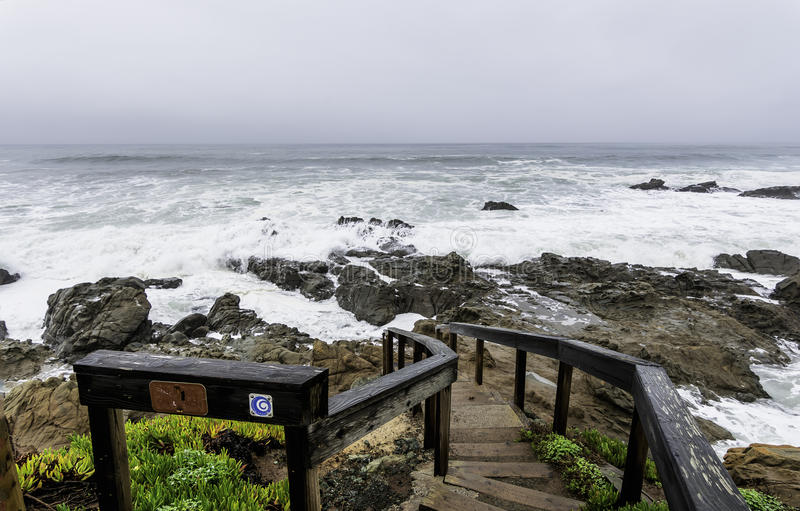Storm surge, steps leading the raging surf. On the California Central Coast, near Cambria, CA stock images