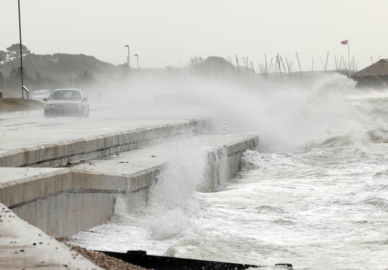 Storm on the waterfront. Waves break over a sea wall and engulf a passing motorist during winter storms stock images