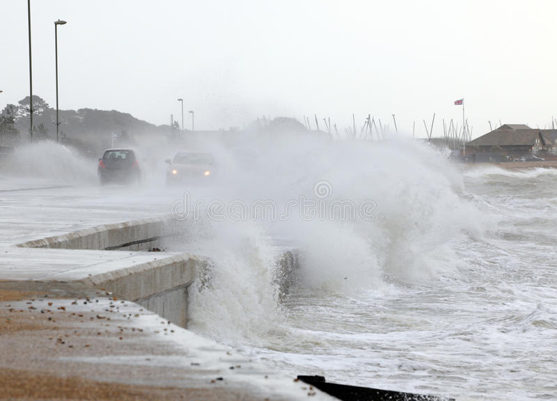 Storm on the waterfront. Waves break over a sea wall and engulf a passing motorists during winter storms royalty free stock photo