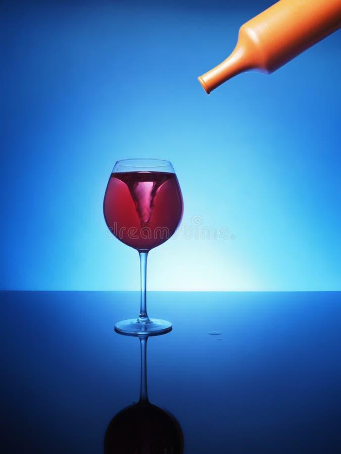 Storma i ett exponeringsglas av rött vin på en blå bakgrund royaltyfri bild