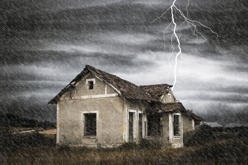 Storma med regn och en åskvigg över ett läskigt gammalt övergett hus royaltyfri foto