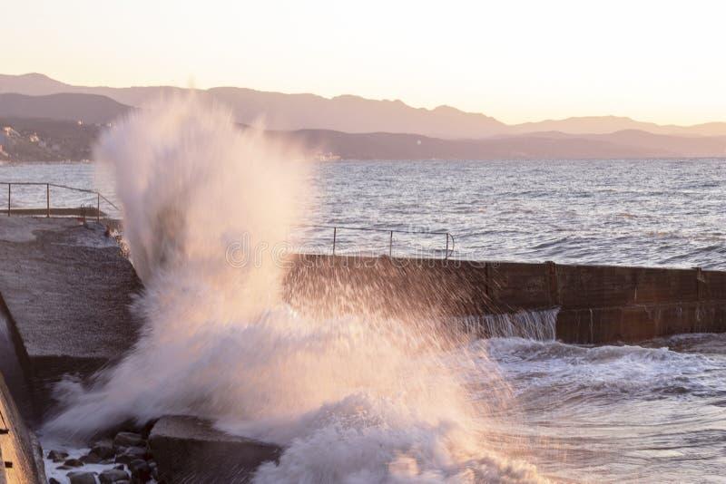 Storma på stranden i solnedgångstrålarna arkivbilder