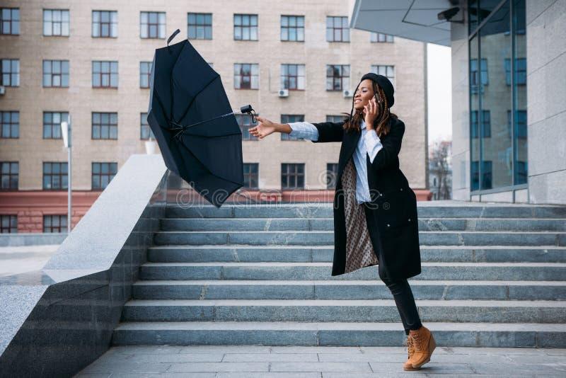 Stormachtig weer De zwarte vliegende paraplu van de meisjesvangst stock afbeeldingen