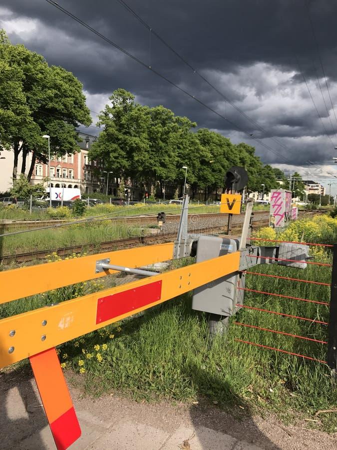 Stormachtig weer en donkere wolken over een spoorwegovergang op stedelijk gebied Uppsala, Zweden royalty-vrije stock foto's