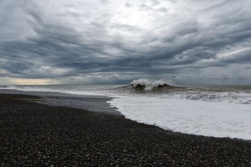 Stormachtig weer - grijze hemel met zware donkere wolken over woedende overzees stock afbeeldingen
