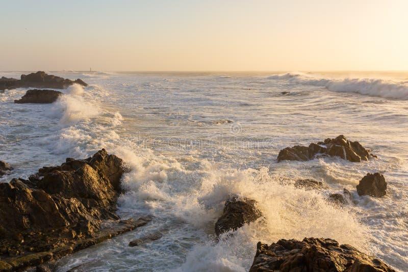 Stormachtige golven die over rotsachtige kust verpletteren stock afbeeldingen