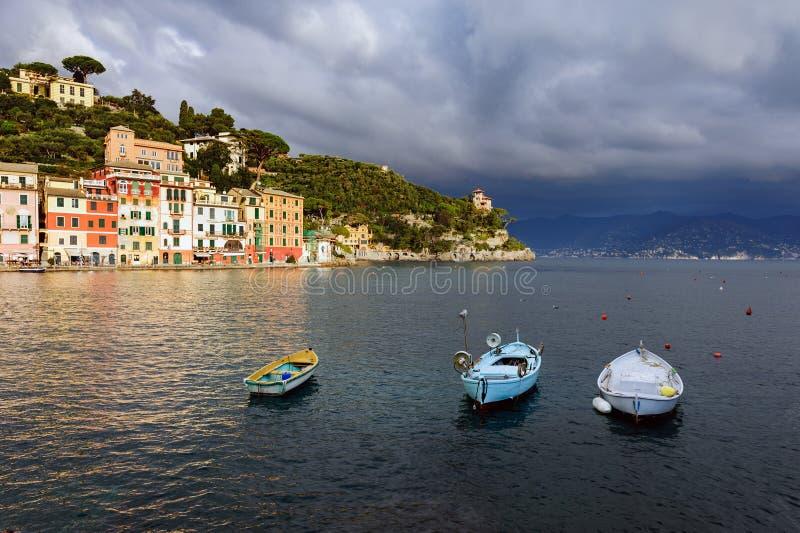 Stormachtige hemel en kleine boten in overzeese baai van Portofino-stad Portofino is kleine visserijstad in het district van Ligu stock foto