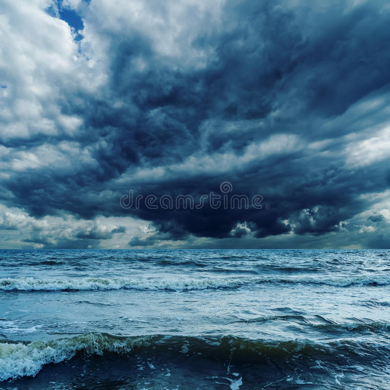 Stormachtige hemel over donkere overzees stock afbeeldingen
