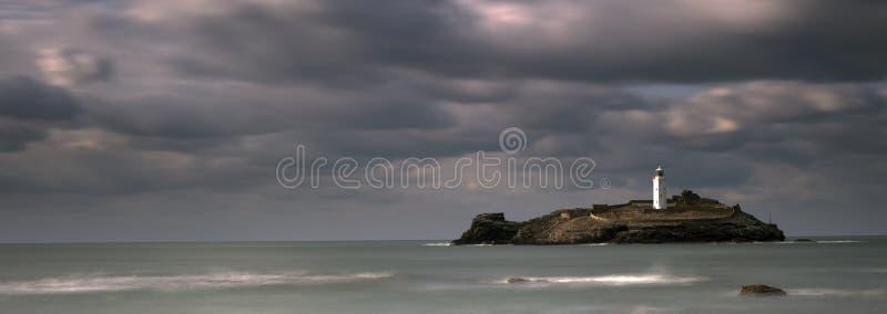 Stormachtige hemel over Godrevy-Vuurtoren op Godrevy-Eiland in St Ives Bay met het strand en rotsen in voorgrond, Cornwall het UK stock foto's