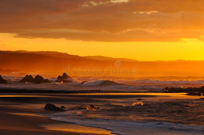 Stormachtige november strandzonsondergang stock foto