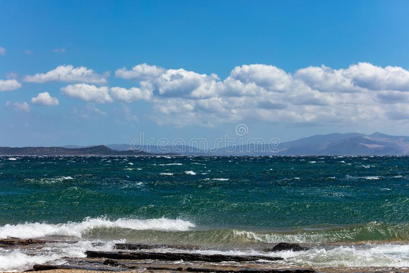 Stormachtige overzees, golven die op rotsen, blauwe hemel met wolkenachtergrond bespatten royalty-vrije stock foto