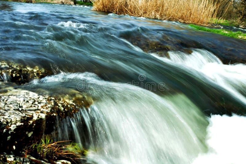Stormachtige rivier met kleine steenstroomversnelling stock afbeeldingen