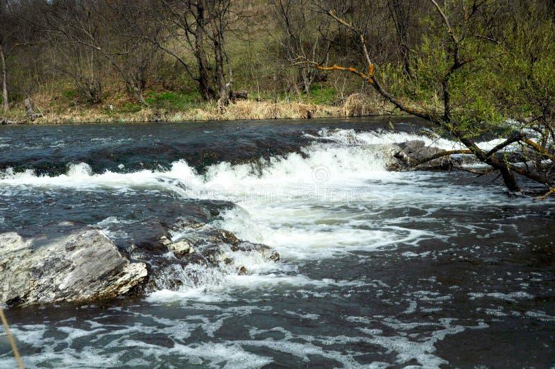 Stormachtige rivier met kleine steenstroomversnelling stock foto's