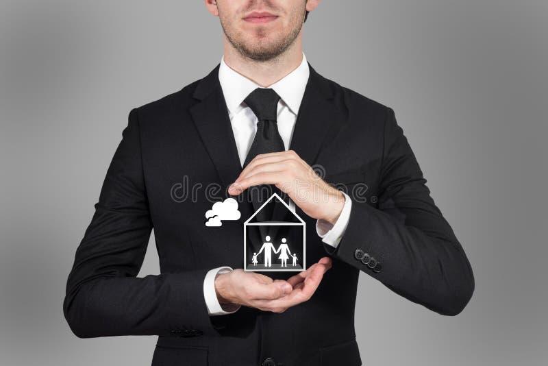 Stormar det skyddande familjanseendet för affärsman i hushänder royaltyfria bilder