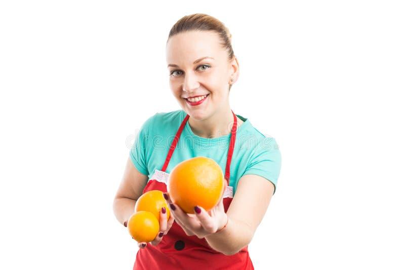 Stormarknad- eller supermarketanställd som rymmer den nya naturliga apelsinen arkivbilder