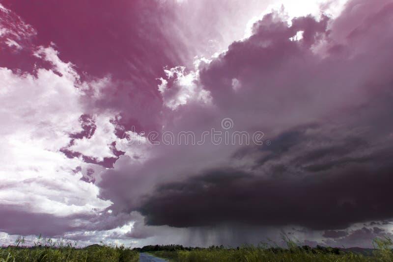 Stormen är kommande regna som framåt jämnt lågt visas av regnmolnet, molnet för än bra väder över vägen och gräsplangulingfältet  royaltyfria foton