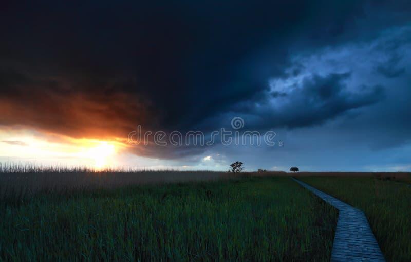 Stormig himmel över träbanan på solnedgången arkivbilder