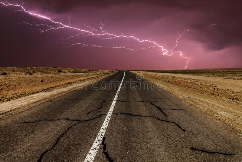 Stormig landsväg på natten, med intensiva blixtslag arkivbilder