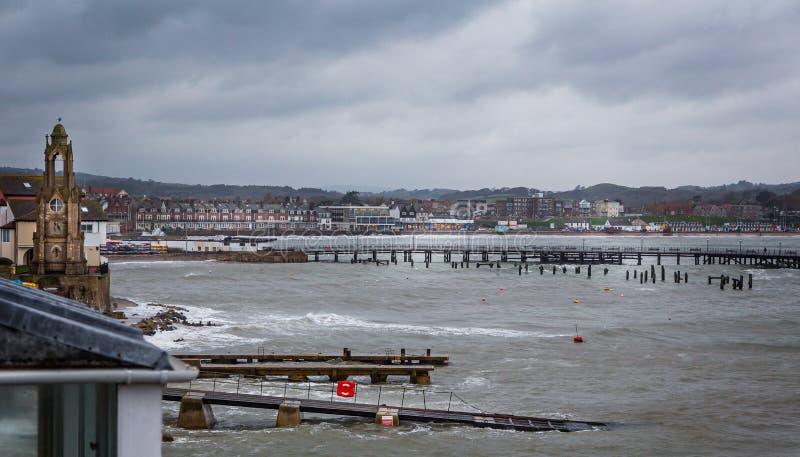 Stormig mulen vinterdag på den Swanage stranden i Dorset, UK royaltyfri foto