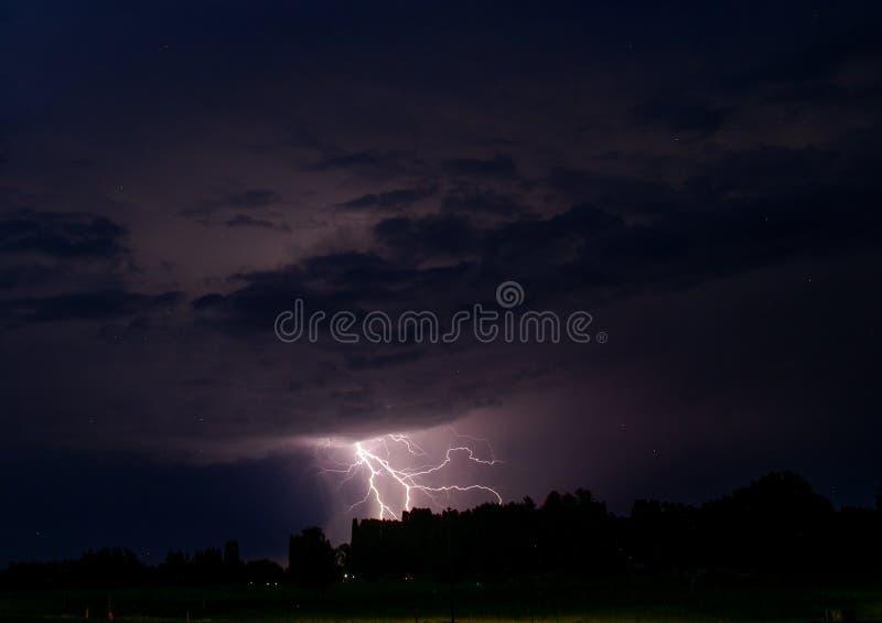 Stormig purpurfärgad himmel med bulten av blixt från himmel till träd i sydliga Minnesota royaltyfri bild