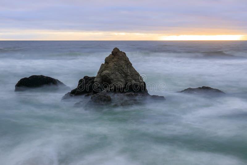 Stormig solnedgång över Gray Whale Cove State Beach royaltyfri foto