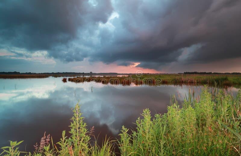 Stormig solnedgånghimmel över den lösa sjön royaltyfri foto