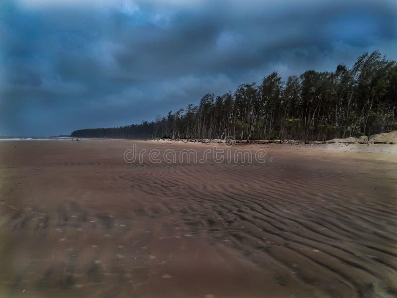 Stormig strand på kusten med molnig sikt arkivbild