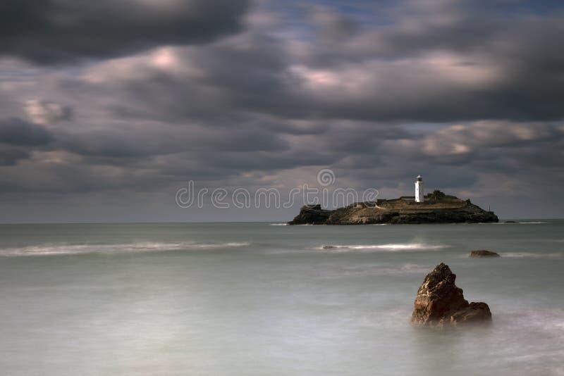 Stormiga himlar över den Godrevy fyren på den Godrevy ön i St Ives Bay med stranden och vaggar i förgrund, Cornwall UK royaltyfria foton