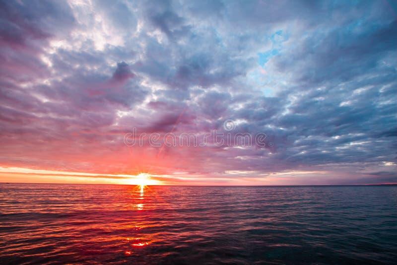 Stormiga moln över lugna vatten med solen som trycker på horisonten Minimalist Seascape royaltyfri foto