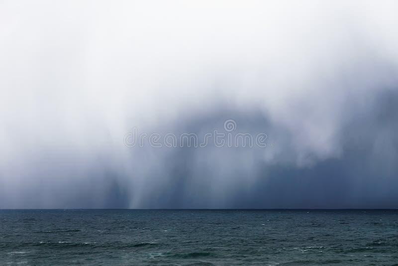 Stormiga moln och regn på havet royaltyfri fotografi