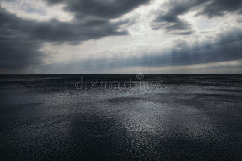 Stormigt grå färg-blått hav och himmel i molnen och strålarna av solen royaltyfri foto