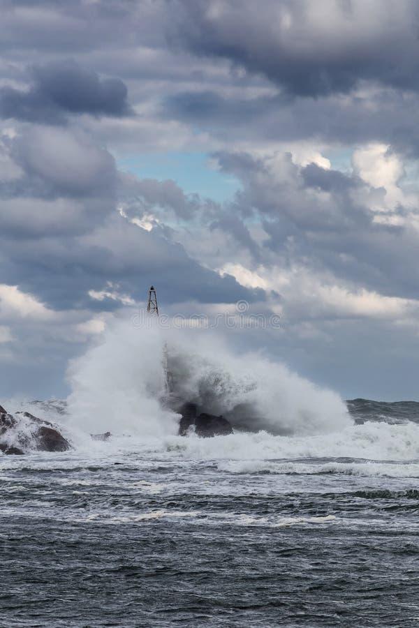 Stormigt hav med stora vågor som kraschar in i fyren royaltyfri bild