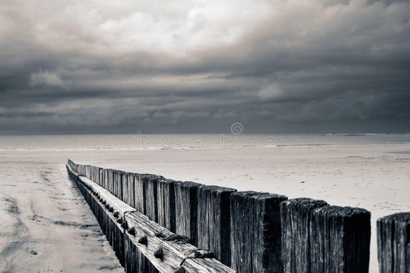 Stormigt strandstaket i monokrom sepia arkivbild