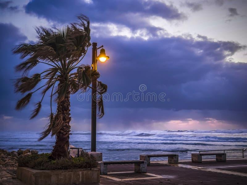 Stormigt vindväder på kusterna av medelhavet, skymning, brinnande lykta royaltyfri foto