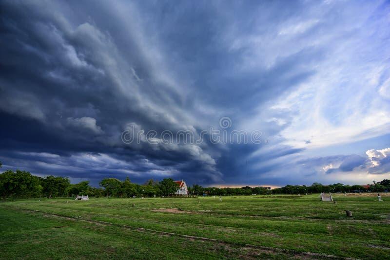 Stormmörker fördunklar att flyga över fält med grönt gräs royaltyfri fotografi