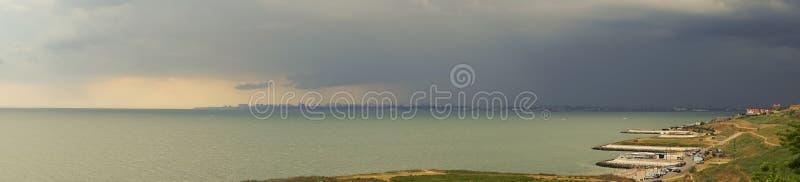 Stormmoln över havet och staden royaltyfri foto