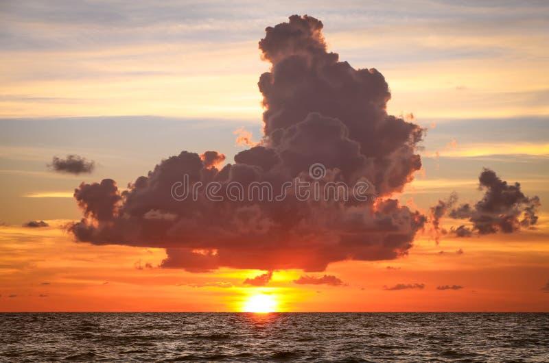 Stormmoln över inställningssolen i havet arkivfoto
