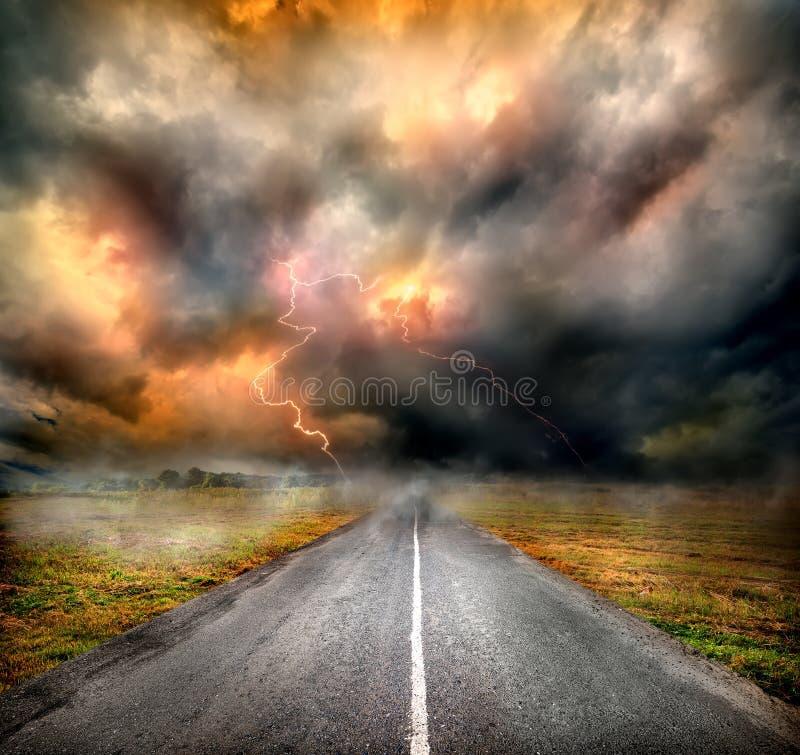 Stormmoln och blixt över huvudvägen arkivfoto