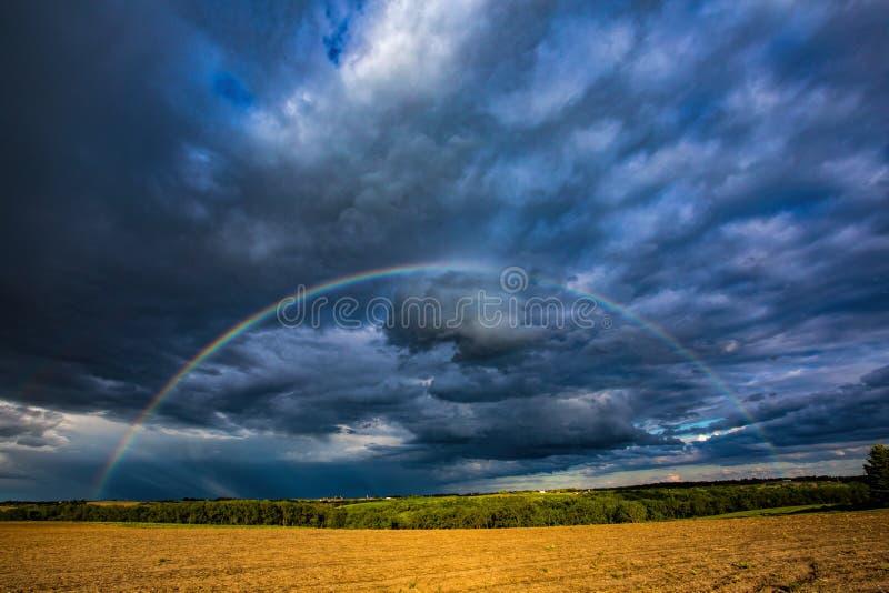 Stormmoln och regnbåge arkivbilder