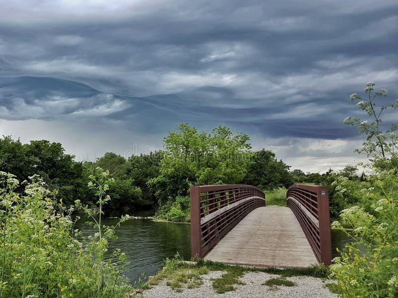 Stormmoln som passerar över en bro royaltyfria foton